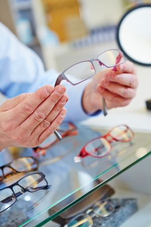 hands of an optician offering new glasses in his retail store photo
