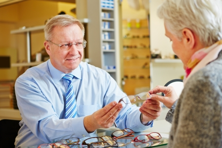 Optician giving consultation to senior woman for new glasses photo