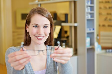 Young happy woman in apprenticeship for optician with new glasses photo