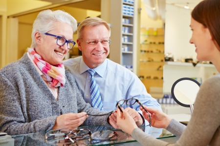 adjust: Optician consulting senior couple for buying new glasses Stock Photo