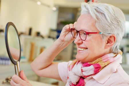 ophthalmic: Happy elderly woman with new glasses looking in a mirror at optician store