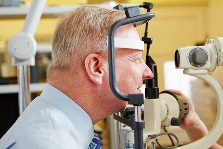 slit: Senior man at eye measurement at ophthalmologist with slit lamp
