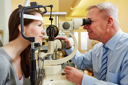 ophthalmologist: Ophthalmologist examing young woman with a slit lamp
