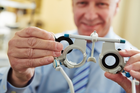 doctor of optometry: Optician with trial frame to determine prescription values of glasses