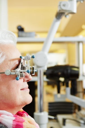 eye exam: Senior Woman with trial frame gets examination at ophthalmologist
