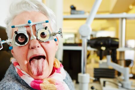 examining: Elderly woman with a trial frame sticking out tongue at the optician