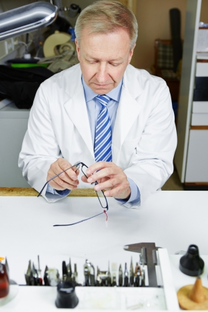 bracing: Optician in workshop fixing glasses with pliers