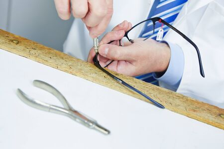 Optician fixing hinge of glasses with a screwdriver photo