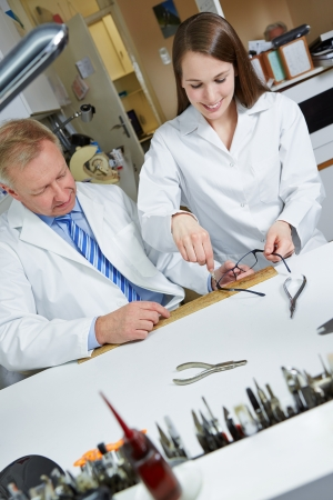 Happy apprentice in workshop of optician fixing glasses with screwdriver photo