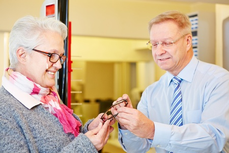 Happy senior woman buying new glasses at the optician photo