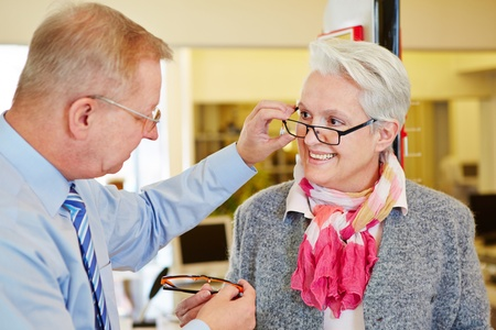 Optician offering consultation to senior woman for new glasses photo