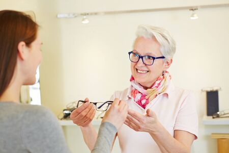 Senior optician giving new glasses to female customer photo