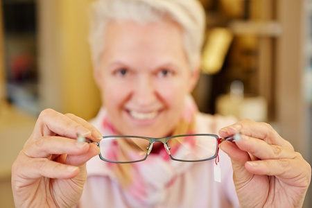 Smiling senior optician holding new glasses in her hands photo