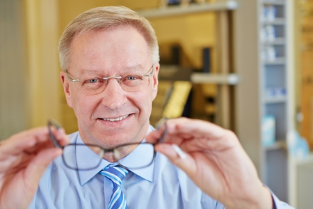 Elderly man as optician holding new glasses photo