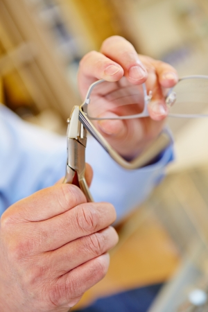 Hand of an optician with pliers reparing glasses photo