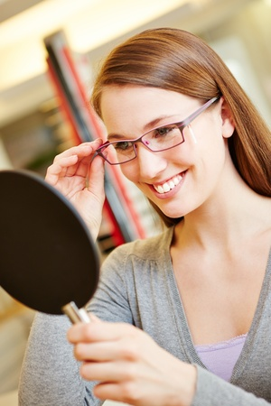 reading glasses: Happy smiling woman with new glasses looking in mirror at optician Stock Photo