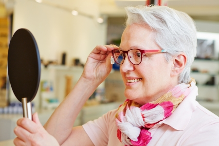 Happy senior woman with new glasses looking in mirror at optician photo