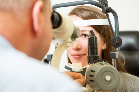 cornea: Optometrist checking eye of young woman with a slit lamp