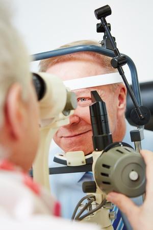 oculista: C�rnea medir oculista del hombre mayor con l�mpara de hendidura Foto de archivo