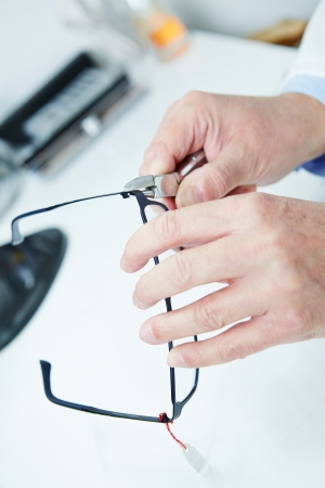 Optician fixing frame of glasses with bending pliers Stock Photo