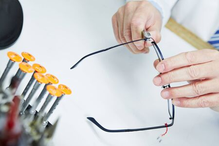 Hand of optician fixing metall jaws of glasses with pliers photo