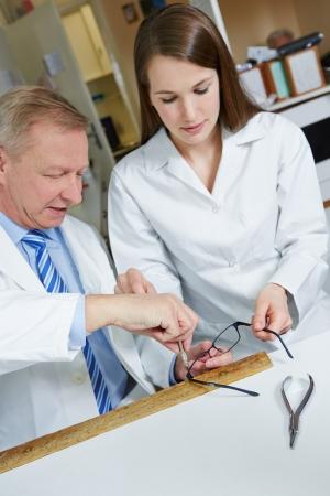 Optician helping trainee in workshop repairing glasses photo