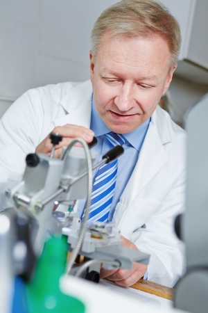rimless: Optician in workshop with drilling machine for rimless glasses