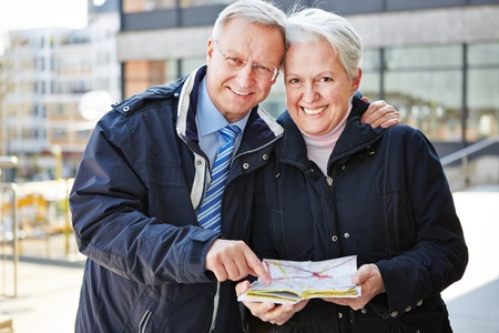 Two happy seniors on city trip with map photo