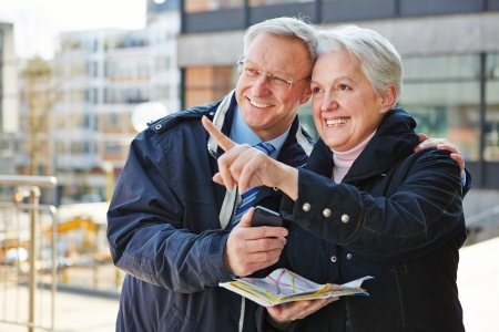 Happy senior couple doing sightseeing tour on city trip with a map photo
