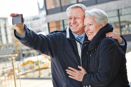 Happy senior couple taking pictures of themselves with a smartphone photo