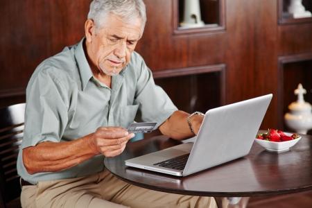 senior ordinateur: Senior homme au portable payer par carte de cr�dit pour faire des achats en ligne Banque d'images