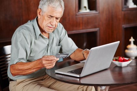 Senior man at laptop paying with credit card for online shopping photo
