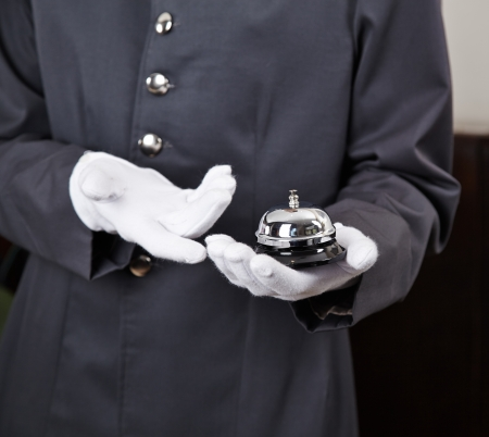 bellhop: Bellboy holding bell in hotel on his hand