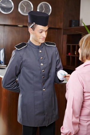 Friendly concierge in hotel giving key card to senior woman Stock Photo - 20104205