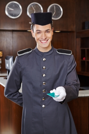bellhop: Happy friendly concierge giving hotel key card Stock Photo