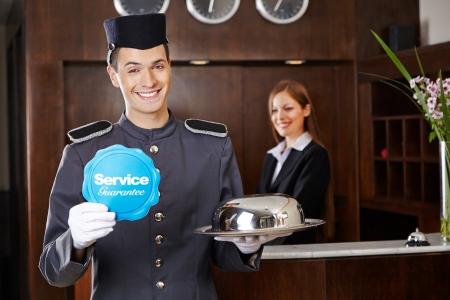 bellhop: Conserje sonriente en la recepci�n del hotel con signo de servicio