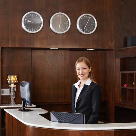 recepcionista: Feliz recepcionista mujer detr�s del mostrador en el hotel