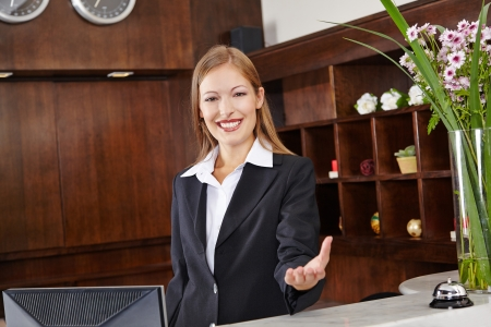 Smiling receptionist behind desk in hotel offers welcome to guest photo