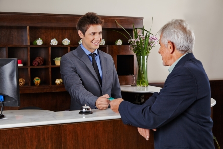 Smiling receptionist behind counter in hotel giving key card to senior guest photo