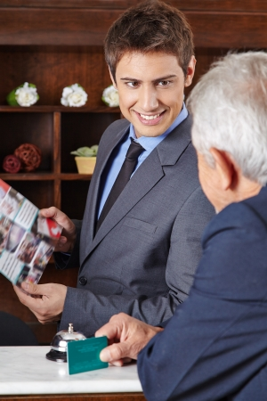 Receptionist in hotel giving brochure to senior guest