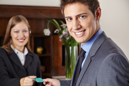 Smiling businessman in hotel getting his key card at the reception Stock Photo - 20278066