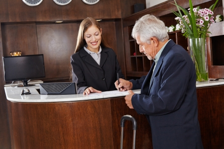 Senior guest signing a form at the hotel reception counter photo
