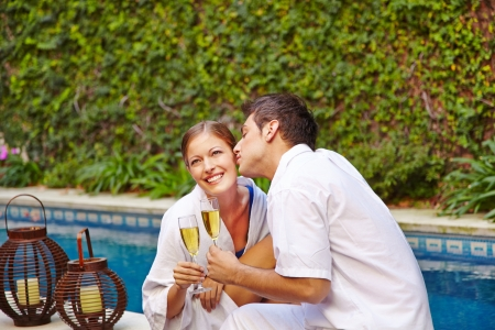 Happy couple in holiday drinking champagne at pool photo