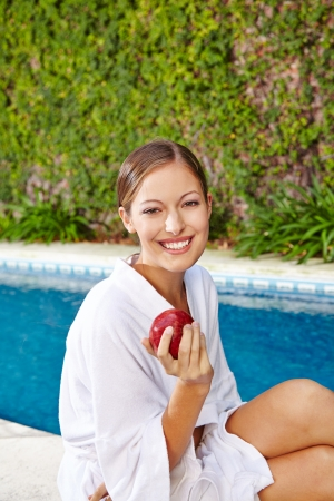 red bathrobe: Young attractive woman with red apple at swimming pool
