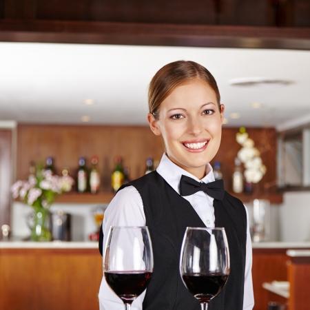 alcohol server: Smiling female waiter serving glasses of red wine in restaurant Stock Photo