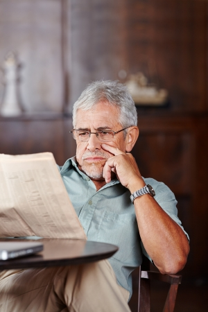 oude krant: Senior man leest een krant aan tafel in rusthuis Stockfoto