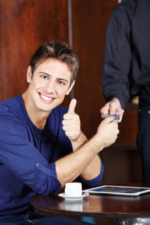 service card: Young man paying with credit card in caf� and holding his thumb up