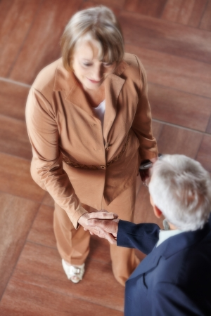 Two senior business people making handshake with focus on hands photo