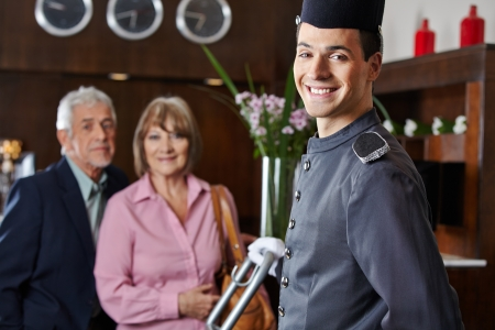 porter: Smiling concierge with senior couple in a hotel Stock Photo