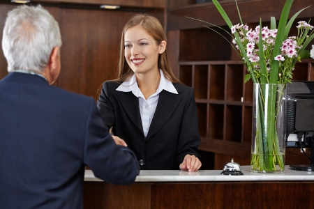 Smiling female receptionist greeting a senior guest with handshake photo